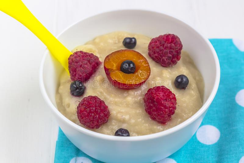 Healthy breakfast porridge for kids. Bowl of baby food on a fabric on white wooden background. The concept of proper nutrition and. Healthy food. close up stock photos