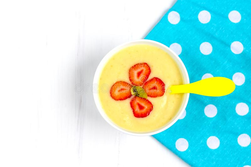 Healthy breakfast porridge for kids. Bowl of baby food on a fabric on white wooden background. The concept of proper nutrition and. Healthy food. Copy space royalty free stock photo
