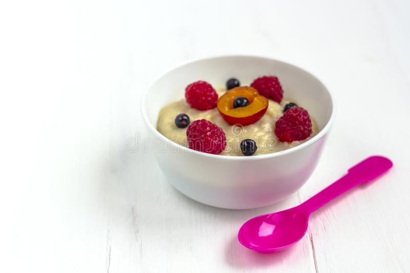 Healthy breakfast porridge for kids. Bowl of baby food on a fabric on white wooden background. The concept of proper nutrition and. Healthy food. Copy space royalty free stock photography