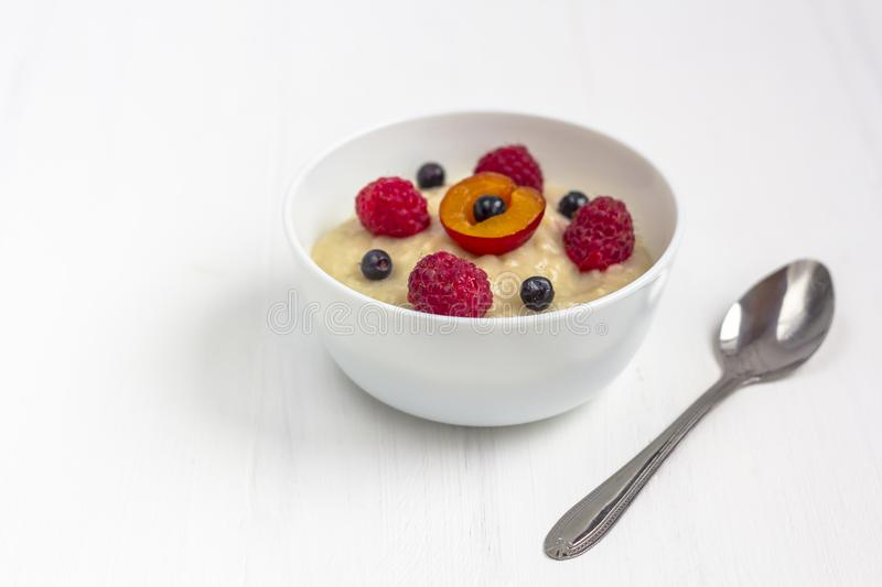 Healthy breakfast porridge for kids. Bowl of baby food on white wooden. Background. The concept of proper nutrition and healthy food. Copy space, close up stock image