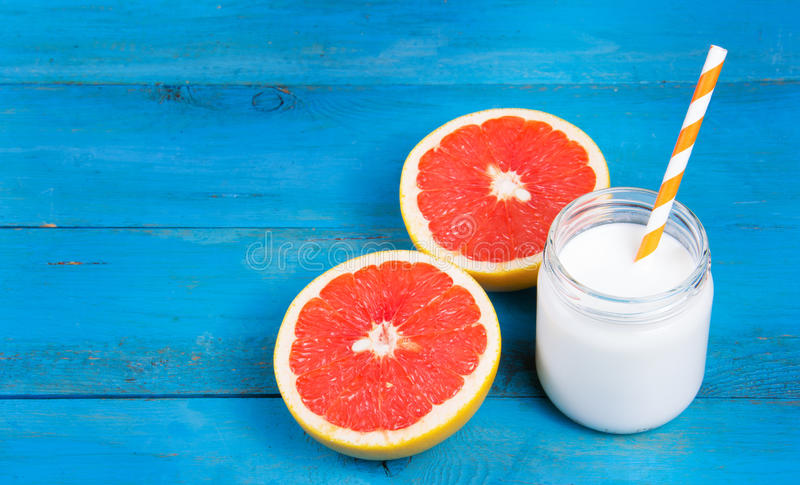 A healthy breakfast, red grapefruit and fresh homemade yogurt on a blue wooden table. stock image
