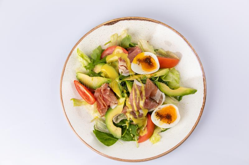 Healthy breakfast. Salad with prosciutto, tomato, egg, avocado. And mustard sauce royalty free stock image