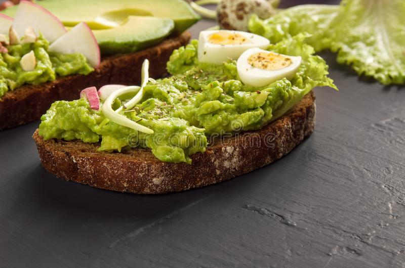 Healthy breakfast. Sandwich with avocado, egg and rye grain bread on black dark table background.Vegetarian food. Close up royalty free stock image