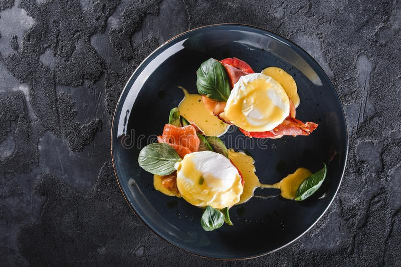 Healthy breakfast sandwiches. Bread toasts with Poached eggs or eggs Benedict, fresh vegetables, avocado, fillet salmon stock photo