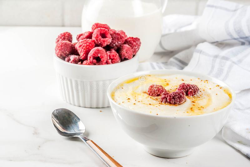 Semolina porridge with raspberry. Healthy breakfast, semolina porridge with milk and raspberry, white marble table copy space royalty free stock image