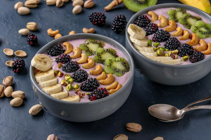 Healthy breakfast smoothie bowl with blackberries, bananas, cashews, kiwi and pistachios on a dark background, horizontal photo stock photos