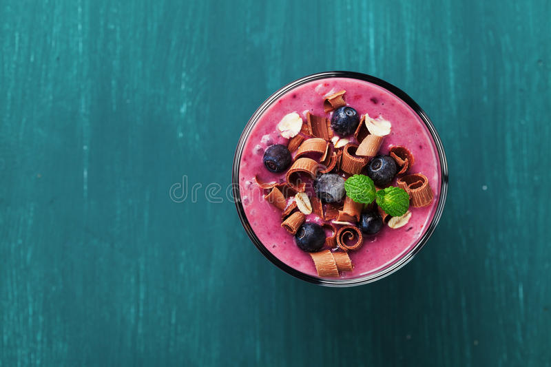 Healthy breakfast of smoothie, dessert, yogurt or milkshake with frozen blueberry and oats decorated grated chocolate and mint. Leaves on wooden rustic table royalty free stock photography