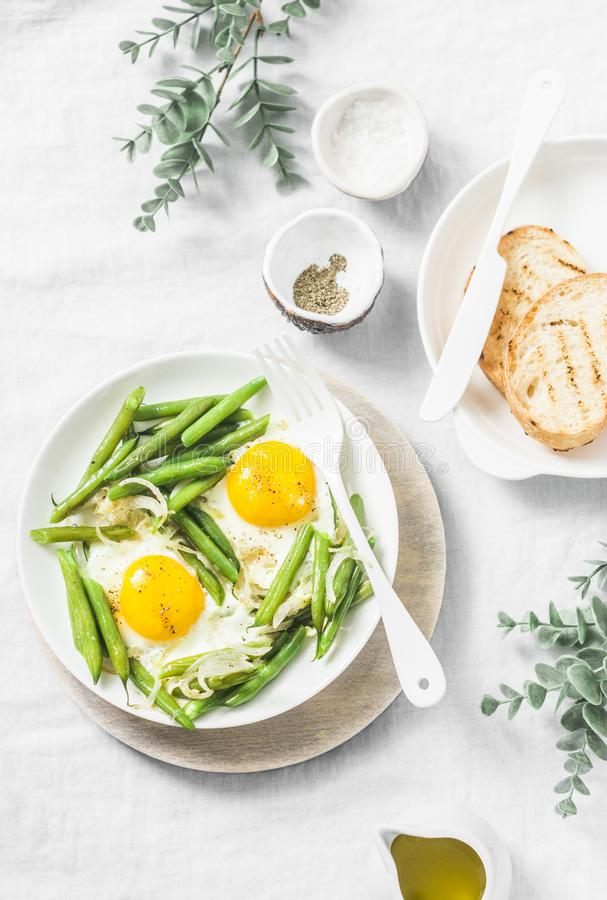 Healthy breakfast or snack - a fried egg with green beans on a light background. Top view stock photos