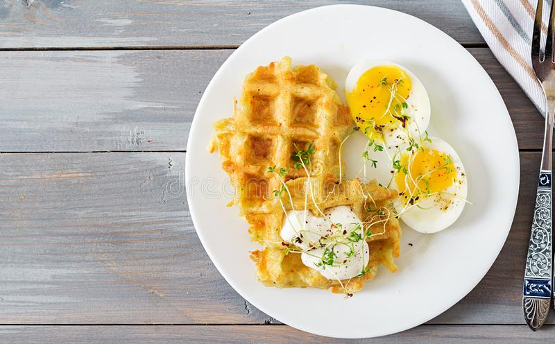 Healthy breakfast or snack. Potato waffles and boiled egg on grey wooden table. Top view. Flat lay stock images