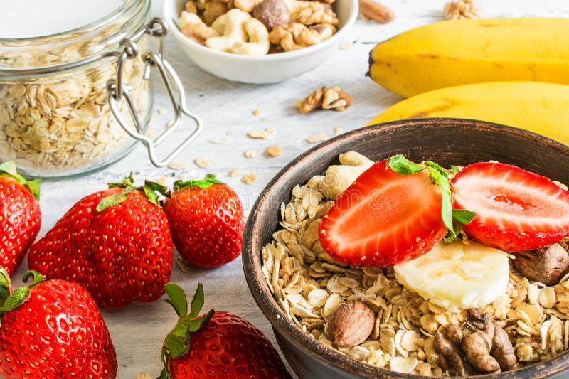 healthy breakfast strawberry and banana muesli with oats, granola and nuts in a bowl royalty free stock photography