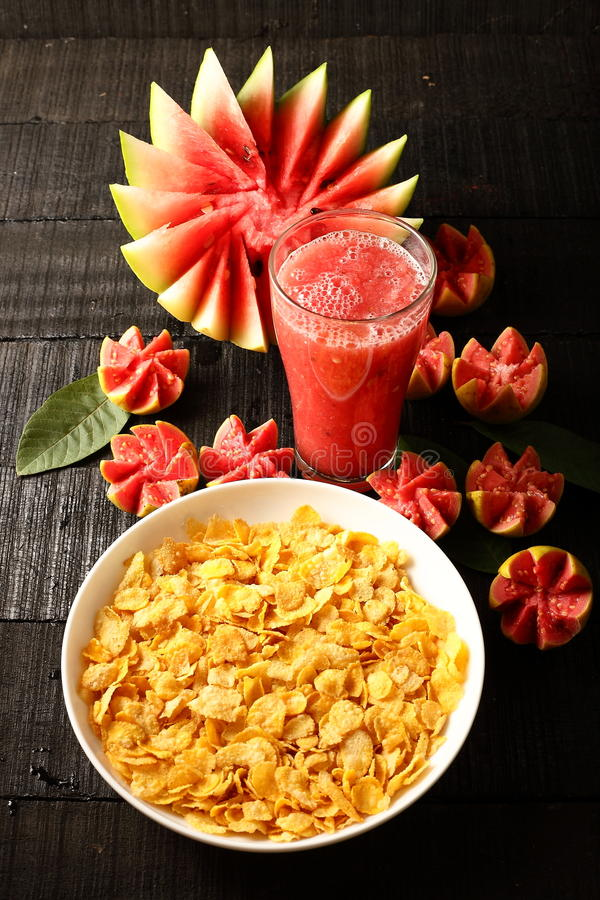 Healthy breakfast table-Corn flakes and fresh juices. Over wooden background stock photography