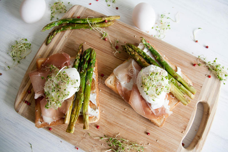 Healthy breakfast. Toast with cream cheese, prosciutto, green asparagus, egg and herbs stock photo