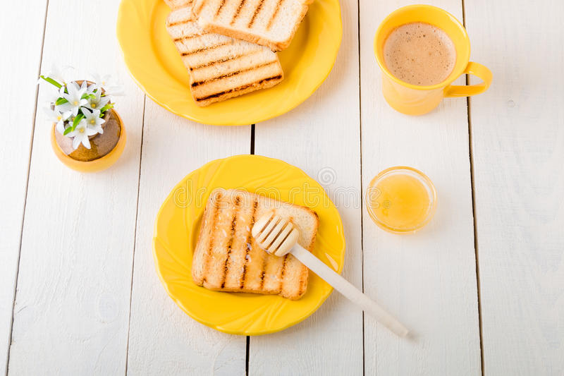 Healthy breakfast with toasted bread and honey near vase with flowers on white background. Yellow tone. Top view. Healthy breakfast with toasted bread and honey stock images