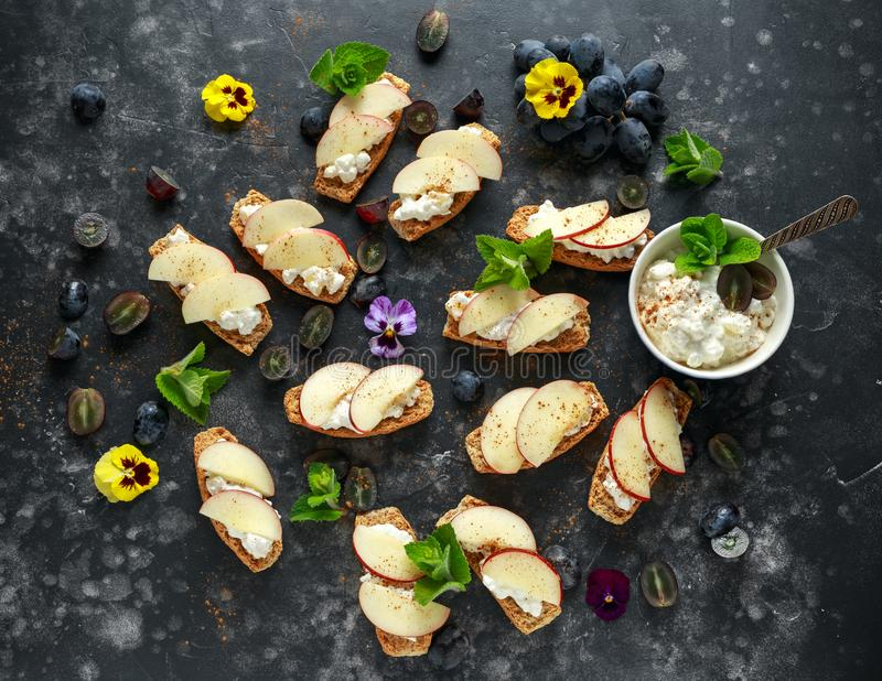 Healthy breakfast toasts with cottage cheese and nectarine slices, sprinkled with cinnamon, served with dark grapes and. Edible flowers stock photos
