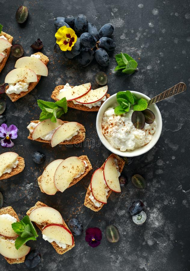 Healthy breakfast toasts with cottage cheese and nectarine slices, sprinkled with cinnamon, served with dark grapes and. Edible flowers royalty free stock photo