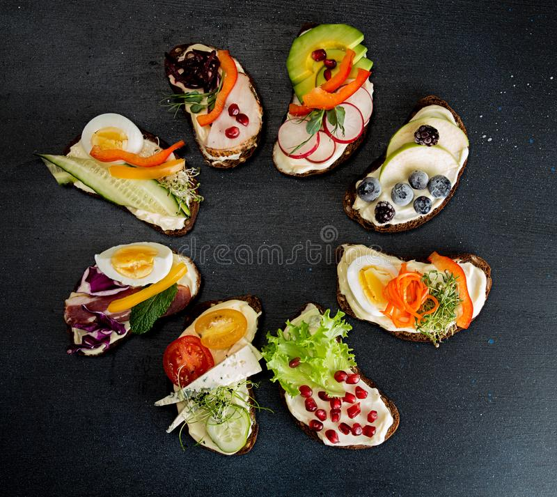 Healthy breakfast toasts with vegetables, fruits , meat and microgreen on dark background. Clean eating healthy food concept. Top. View. Copy space stock images