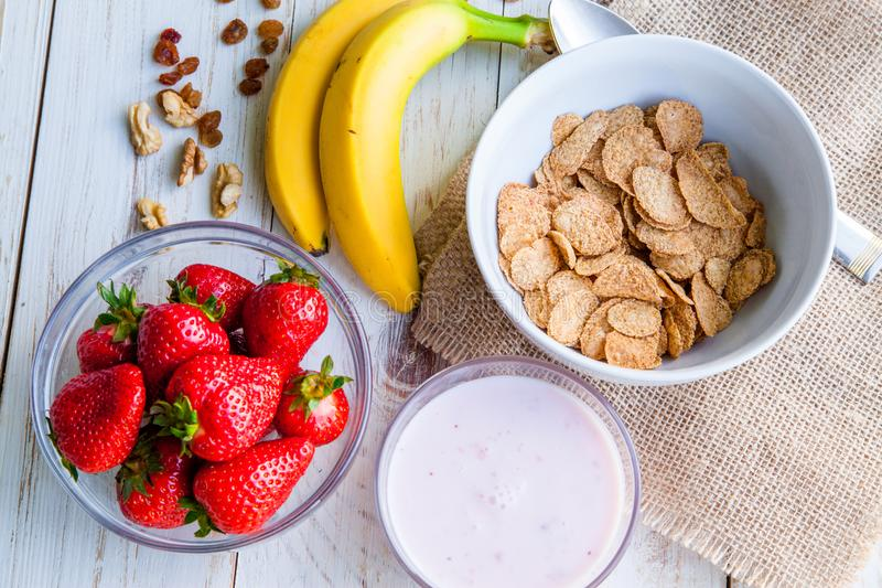 Healthy Breakfast which included cornflakes and oatflakes, yogurt, bananas. And strawberries stock photography
