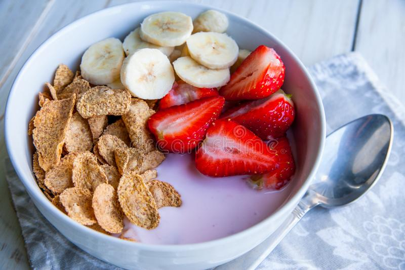 Healthy Breakfast which included cornflakes and oatflakes, yogurt, bananas. And strawberries stock photos