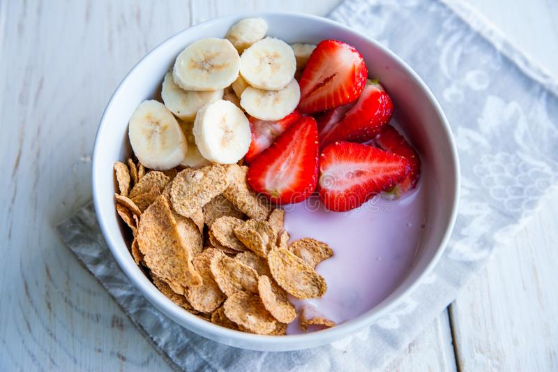 Healthy Breakfast which included cornflakes and oatflakes, yogurt, bananas. And strawberries stock images