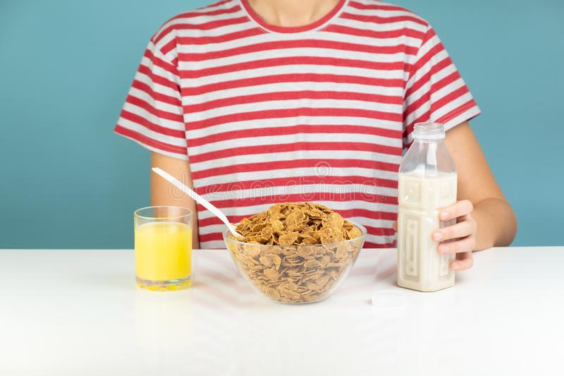 Healthy breakfast with whole grain cereals, milk and juice. Illustrative minimalistic image of vegetarian food on the table and h royalty free stock photography