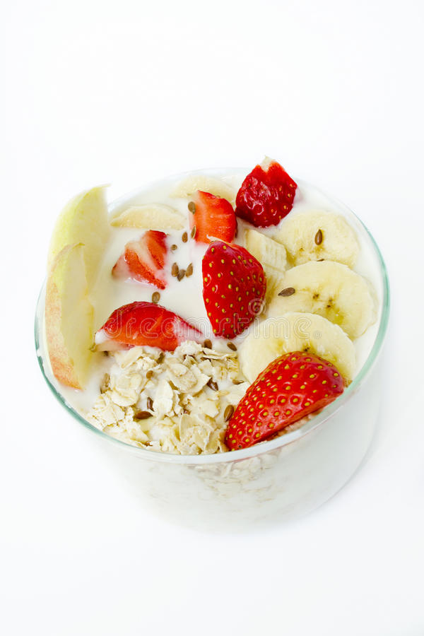 Healthy breakfast - yogurt, oat flakes, strawberries, bananas, apples, flax seeds. White background. royalty free stock photos
