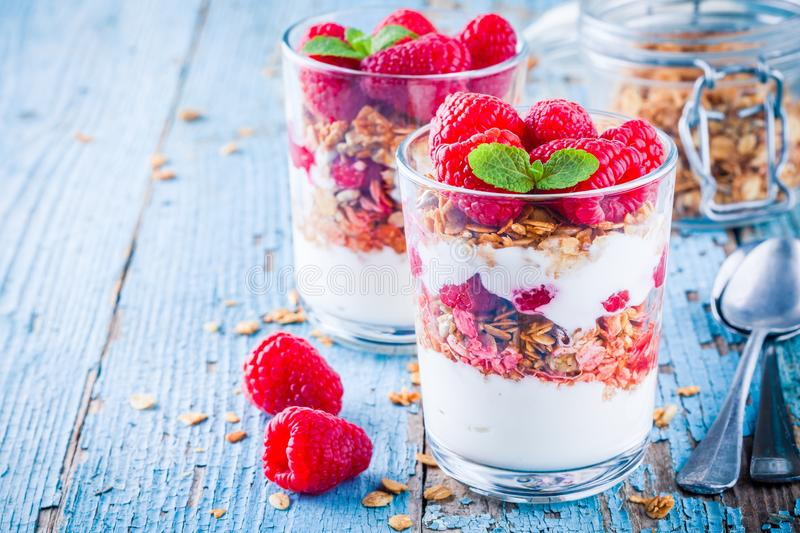 Healthy breakfast: yogurt parfait with granola and fresh raspberries. On rustic background stock photography