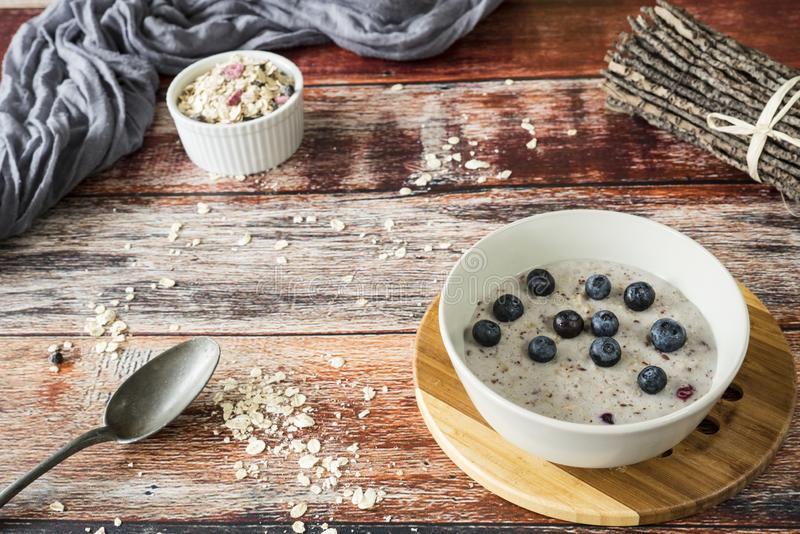 Healthy breakfeast with oats, quinoa, blueberries, on wooden table stock image