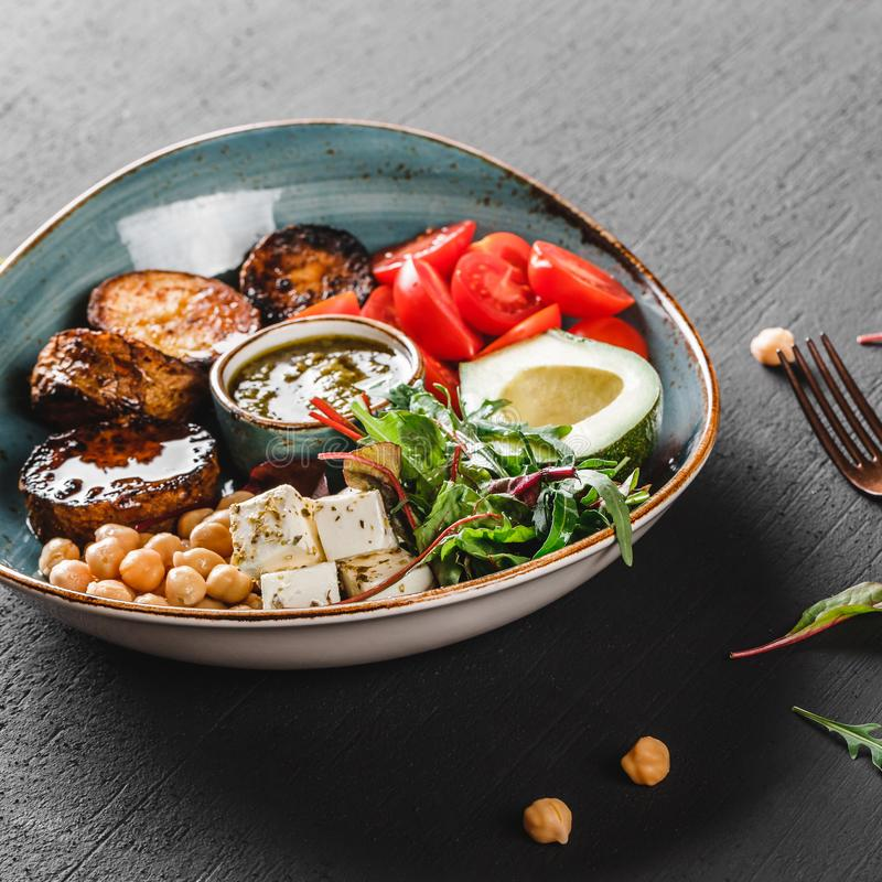 Healthy Buddha bowl dish with avocado, tomato, cheese, chickpea, fresh arugula salad, baked potatoes and sauce pesto on background. Healthy Buddha bowl dish with stock images