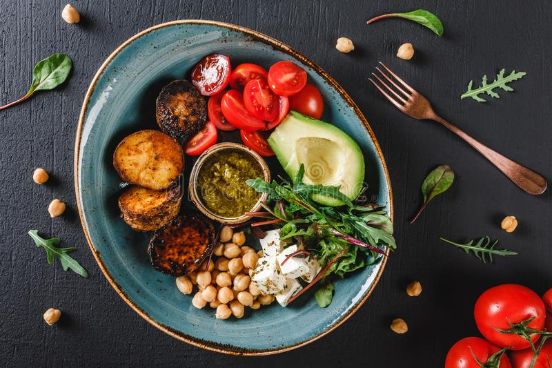 Healthy Buddha bowl dish with avocado, tomato, cheese, chickpea, fresh arugula salad, baked potatoes and sauce pesto. In black background. Dieting food, clean stock photos