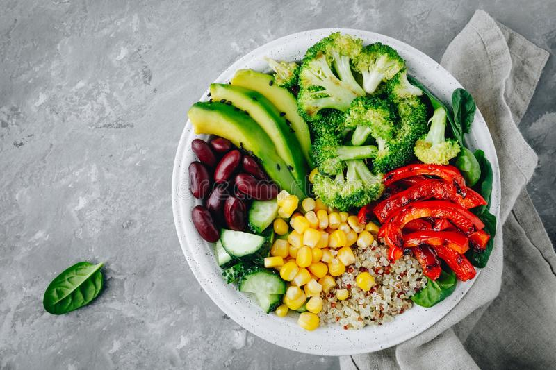 Healthy buddha bowl salad with grilled vegetables. Quinoa, spinach, avocado, beans, sweet corn, broccoli, cucumbers and paprika stock photos