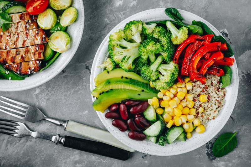 Healthy buddha bowl salad with grilled vegetables. Quinoa, spinach, avocado, beans, sweet corn, broccoli, cucumbers and paprika royalty free stock photography