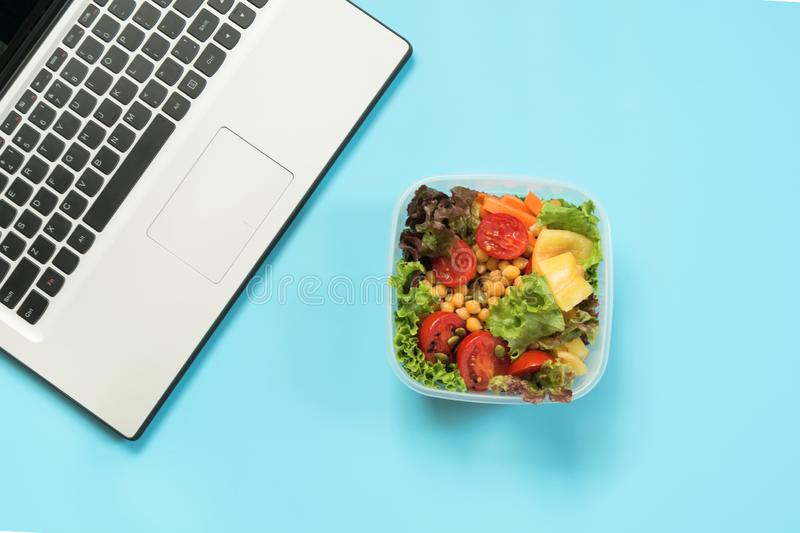 Healthy business lunch in the office, salad for snack on blue table. Top view with copy space. Concept proper nutrition. Take away stock image