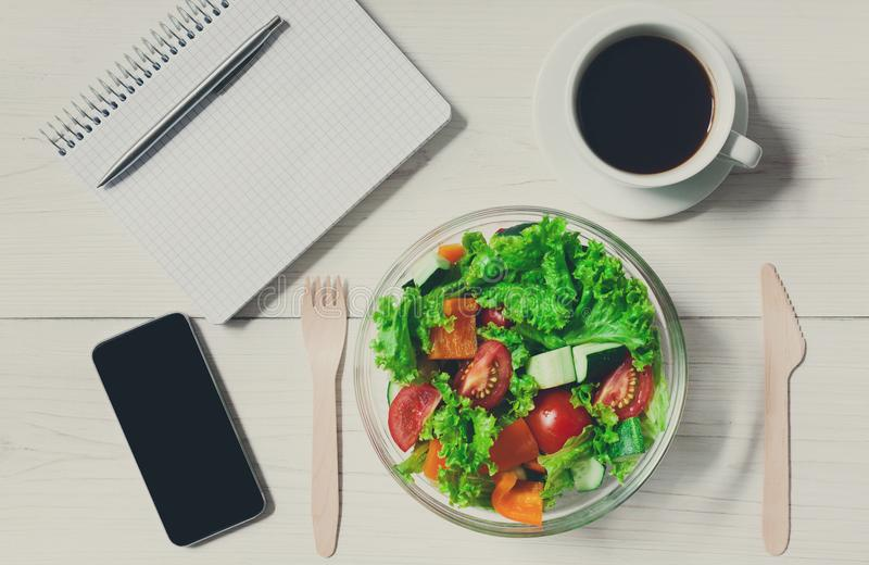 Healthy business lunch snack in office, vegetable salad bowl. Healthy lunch in office, diet concept. Salad and black coffee at workplace near mobile phone and stock image