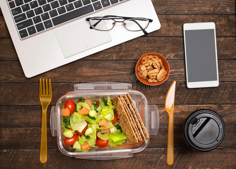 Healthy business lunch at workplace. Salad, salmon, avocado and nuts lunch box on working desk with laptop, smartphone, glasses stock image