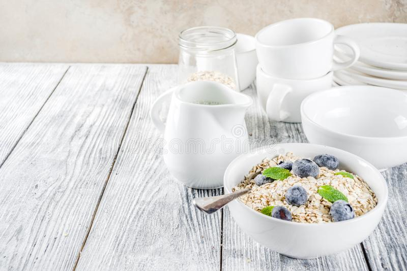 Healthy cereal and milk breakfast concept. Dry oats in small bowl, with milk and fresh blueberry, white  wooden concrete background copy space stock photography