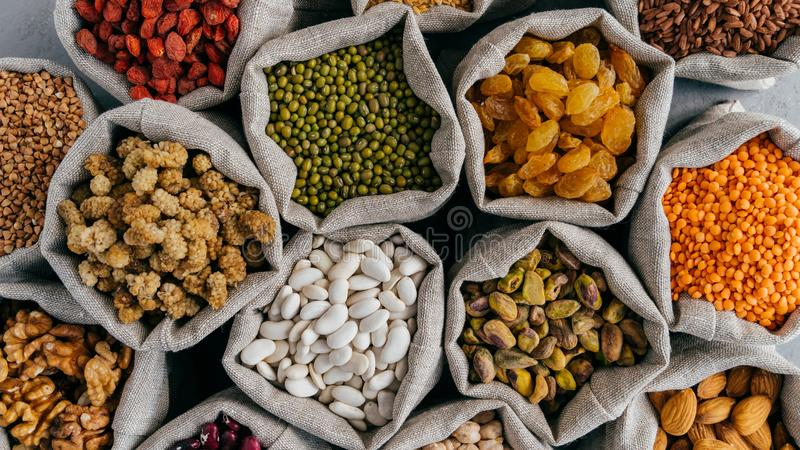 Healthy cereals and dried fruit. Close up top view of small bags with dry legumes seeds. Different types of beans. Natural grains royalty free stock photography