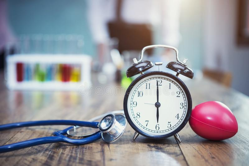 Healthy checking plan concept. Alarm clock with medical instruments stethoscope and red heart on wood table and blurred science l stock photos
