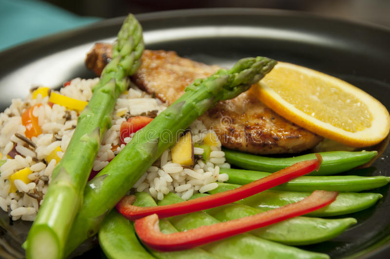 Healthy chicken meal. This is a healthy chicken meal with a light glaze, vegetables and rice stock photos