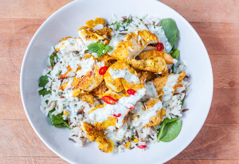Healthy chicken meal. Tandoori chicken, rice and spinach dish in a white bowl stock images