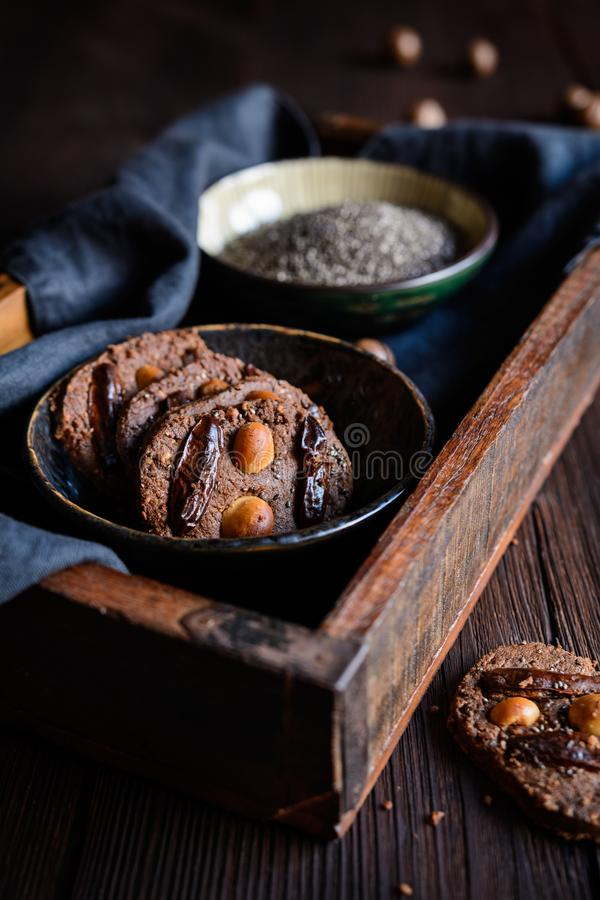 Chocolate chia seeds cookies topped with dried dates and macadamia nuts royalty free stock image