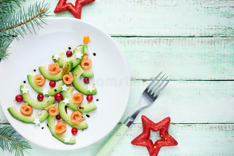 Healthy Christmas appetizer snack - avocado salmon cranberry Christmas tree royalty free stock photo