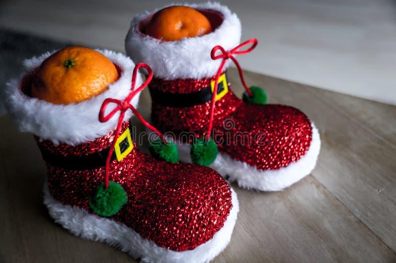 Healthy Christmas treat. Mandarin in Santa shoe. royalty free stock image