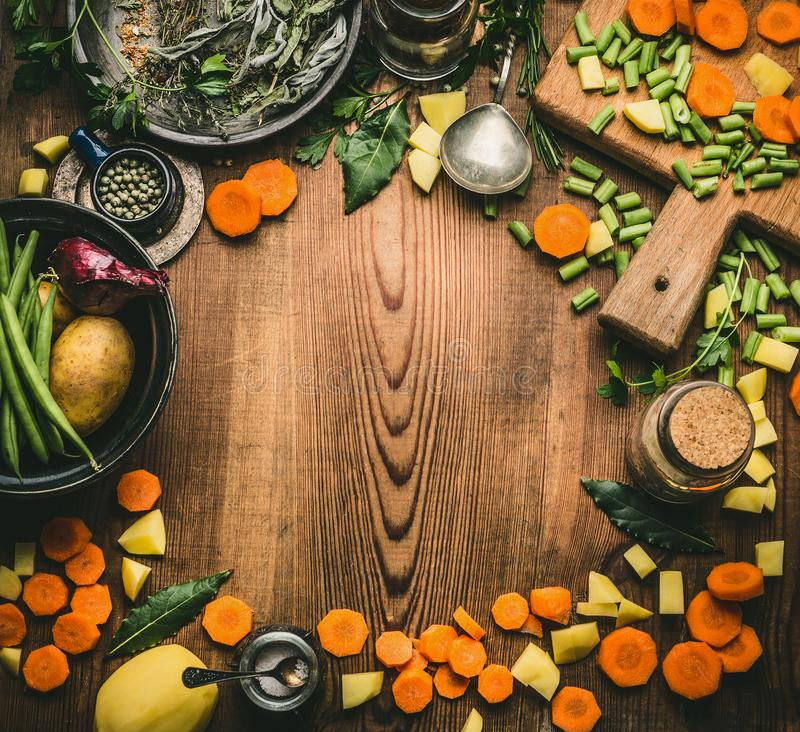Healthy clean cooking and eating concept. Kitchen table from above with various ingredients: chopped vegetables, herbs and spices, royalty free stock image