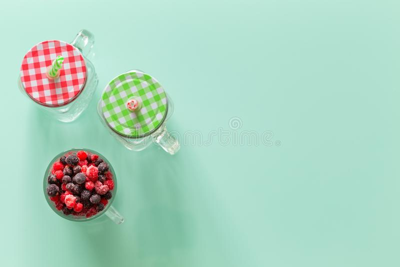 Healthy cocktail of forest fruits on a background of pastel green glass top, Empty space for an inscription stock photo