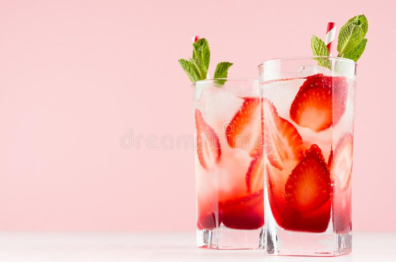 Healthy cold fruit beverage with strawberry and mineral water, mint, ice, straw in modern elegant pastel pink interior, copy space stock image