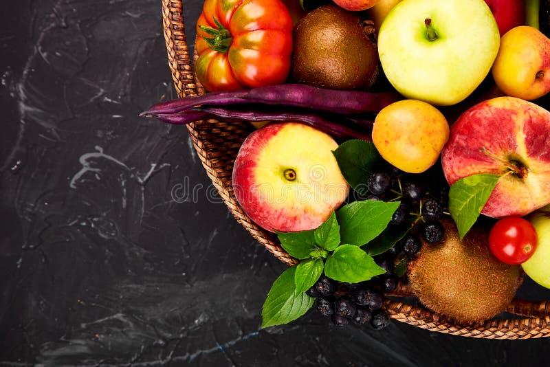 Healthy colorful food selection: fruit, vegetable, superfood, leaf in basket on dark background. Clean eating. Vegan. Detox. royalty free stock photo