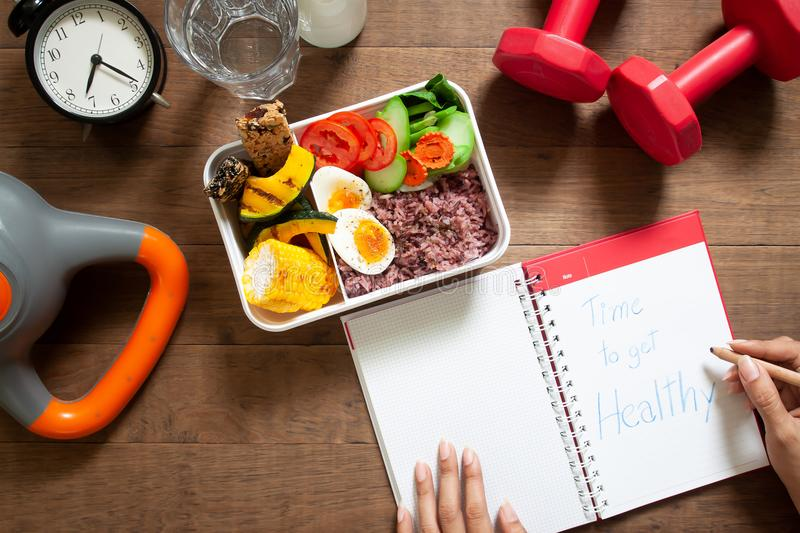 Healthy concept with nutrion food in lunch box and fitness equip. Ments with woman writing time to get healthy on diary book stock photo