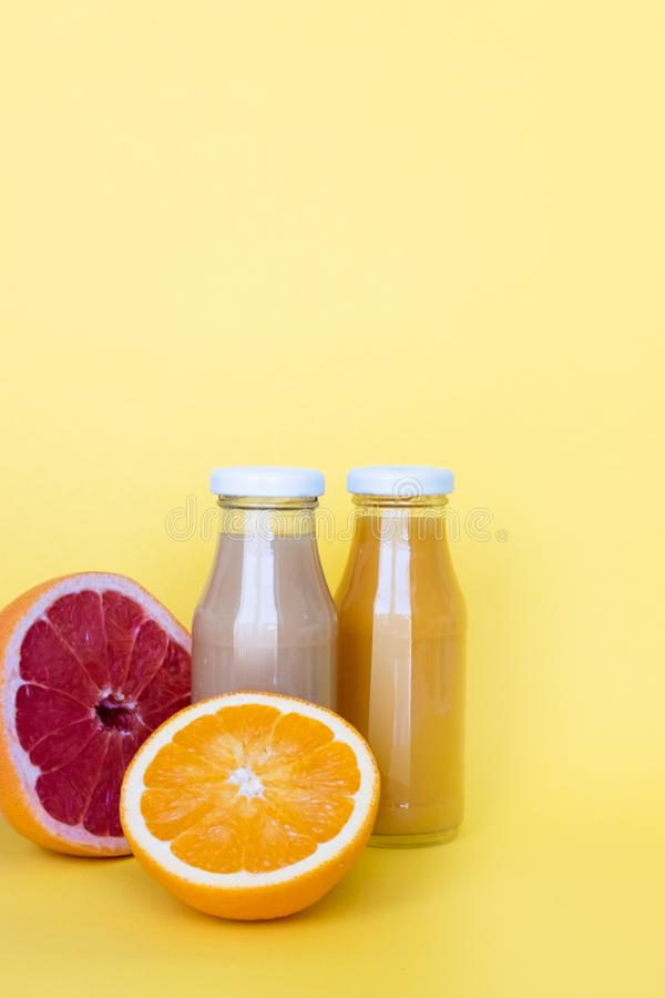 Healthy concept.   Raw fruit juices in glass bottles on yellow background.  Copy space. Healthy concept.   Raw fruit juices in glass bottles on yellow royalty free stock images