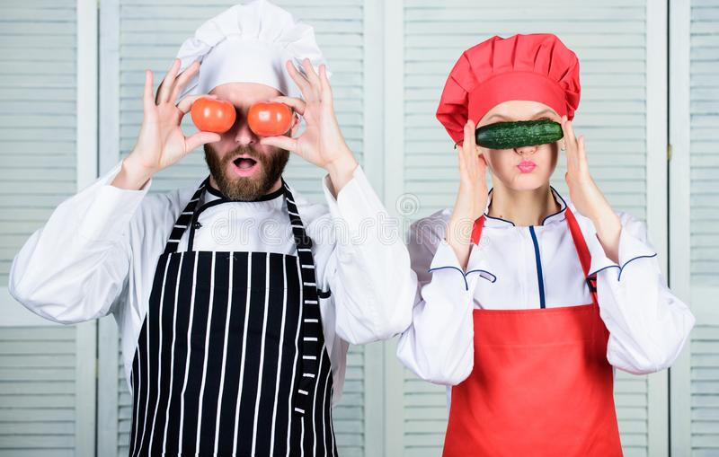 Healthy cooking. Couple of cooks having fun with natural healthy food. Chef and cook helper playing with vegetables in royalty free stock images