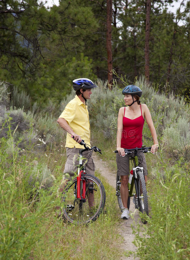 Healthy Couple on Bikes in a Forest. Outdoor photo of healthy young adult couple on bicycles on a trail in the forest stock photos